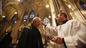 NEW YORK, NY - MARCH 09: Seminarian Richard Marrano (R) distributes ahes to a worshiper during Ash Wednesday services at Saint Patrick's Cathedral on March 9, 2011 in New York City. Ash Wednesday marks the beginning of Lent and involves the placing ashes on the foreheads of Christian believers as a sign of repentance which occurs 40 days, excluding Sundays, before Easter. (Photo by Mario Tama/Getty Images)
