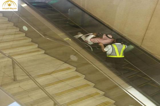 عامل يدفع مُسناً على السلّم الكهربائي بمطار الرياض-صورة