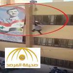 بالفيديو : لحظة سقوط طالب سوري موالي للنظام ميتاً أثناء رفع العلم فوق صورة بشار