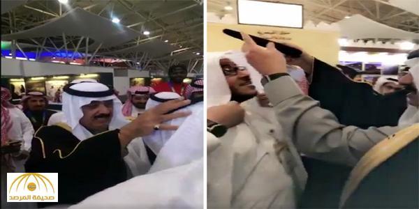 """بالفيديو.. الأمير متعب بن عبدالله يتذوق """"الجريش"""" ويضع """"العقال"""" على رأس مصور"""