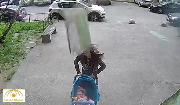 شاهد.. خرسانة مبنى تسقط على رأس سيدة بأحد شوارع روسيا