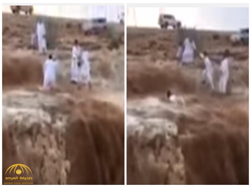 شاهد ماذا حدث لمواطن حاول التقاط صورة لزملائه وسط السيول الجارفة على حافة أحد الوديان؟