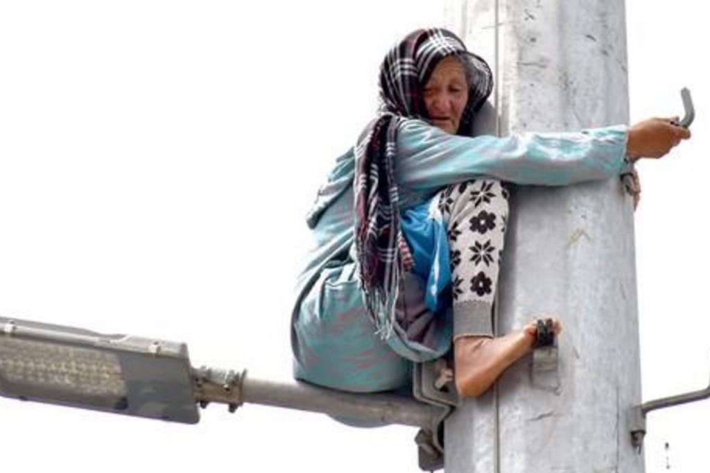 بالفيديو والصور : بعد الاحتيال والاستيلاء على أرضها .. عجوز مغربية تتسلق عمود إنارة وتهدد بالانتحار