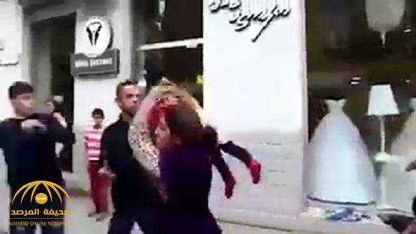 """شاهد : امرأة تضرب رجلاً في شارع عام .. وسلاحها """"طفل"""""""