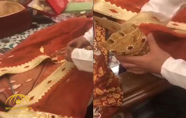 """شاهد: لحظة تجهيز """"بشت"""" مشنشل بقطع الذهب الكبيرة ليرتديه فنان كويتي أثناء إحياء حفل غنائي!"""