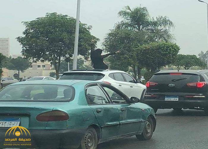 شاهد بالصور .. فتاة مصرية ترقص على سقف سيارتها وسط شارع بالقاهرة !