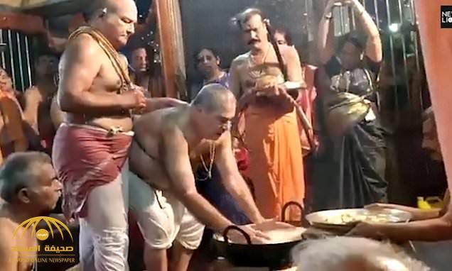 """شاهد  .. غمس أيدي مجموعة من المصلين في الزيت """"المغلي"""" داخل معبد هندي تقرباً للآلهة!"""
