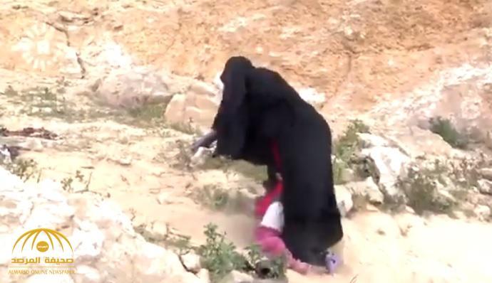 """مشهد صادم.. """"داعشية"""" تجرّ أطفالها على الصخور بعد خروجها من الباغوز في سوريا (فيديو)"""