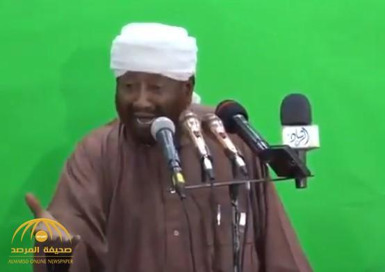 """بالفيديو.. """"واعظ سوداني"""" يبصق على المتظاهرين في السودان ويشتمهم: """"قوم يا وسخ شوف شغلك""""!"""