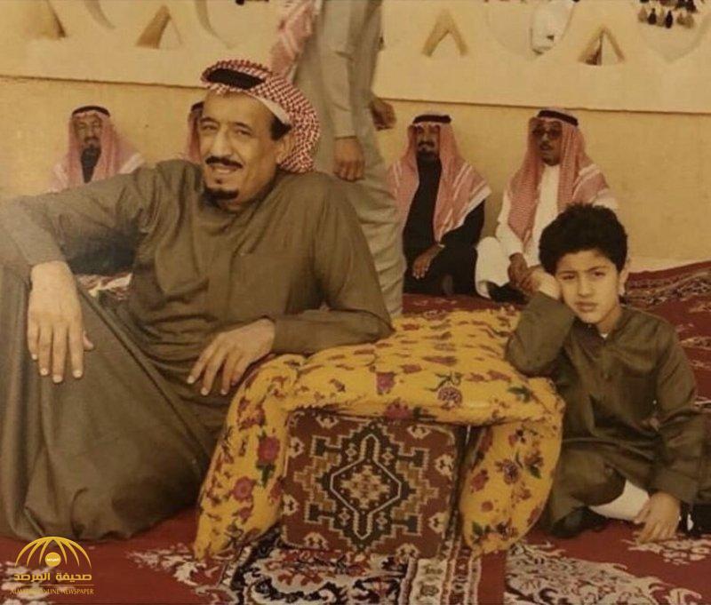 الكشف عن هوية الطفل الجالس بجوار خادم الحرمين في الصورة النادرة