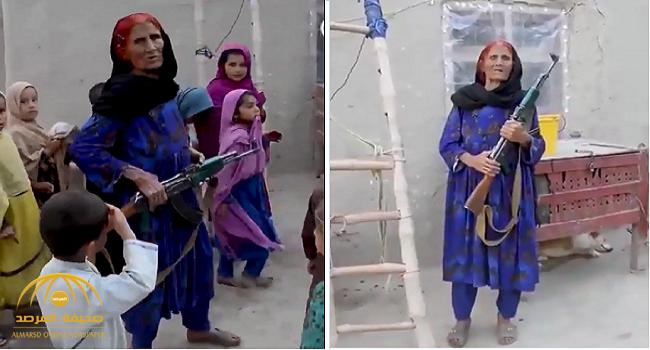 """شاهد عجوز أفغانية تفاجئ المارة بـ """"الكلاشنكوف"""".. لديها سبب غريب لحمله دائما وسط الأطفال !"""