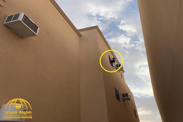 بالصور .. شاهد كيف انتهت مغامرة طفل بعد أن علق في نافذة منزله بالطابق الثالث في القصيم