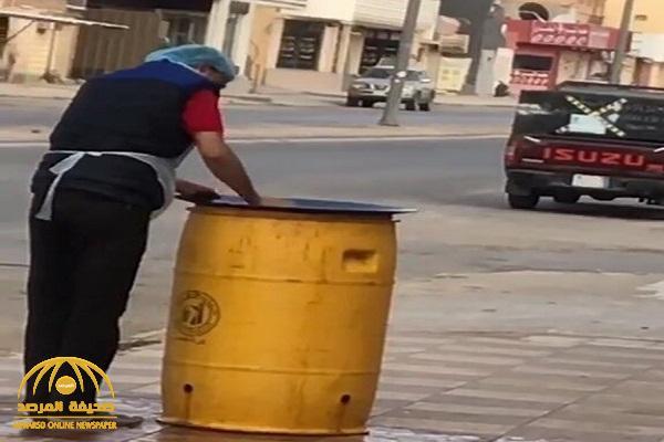 شاهد .. عامل بمطعم في حفر الباطن يغسل الصحون فوق برميل نفايات !