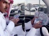 شاب قطري يلقي الأموال من شباك السيارة.. شاهد ردة فعل أحد المارة